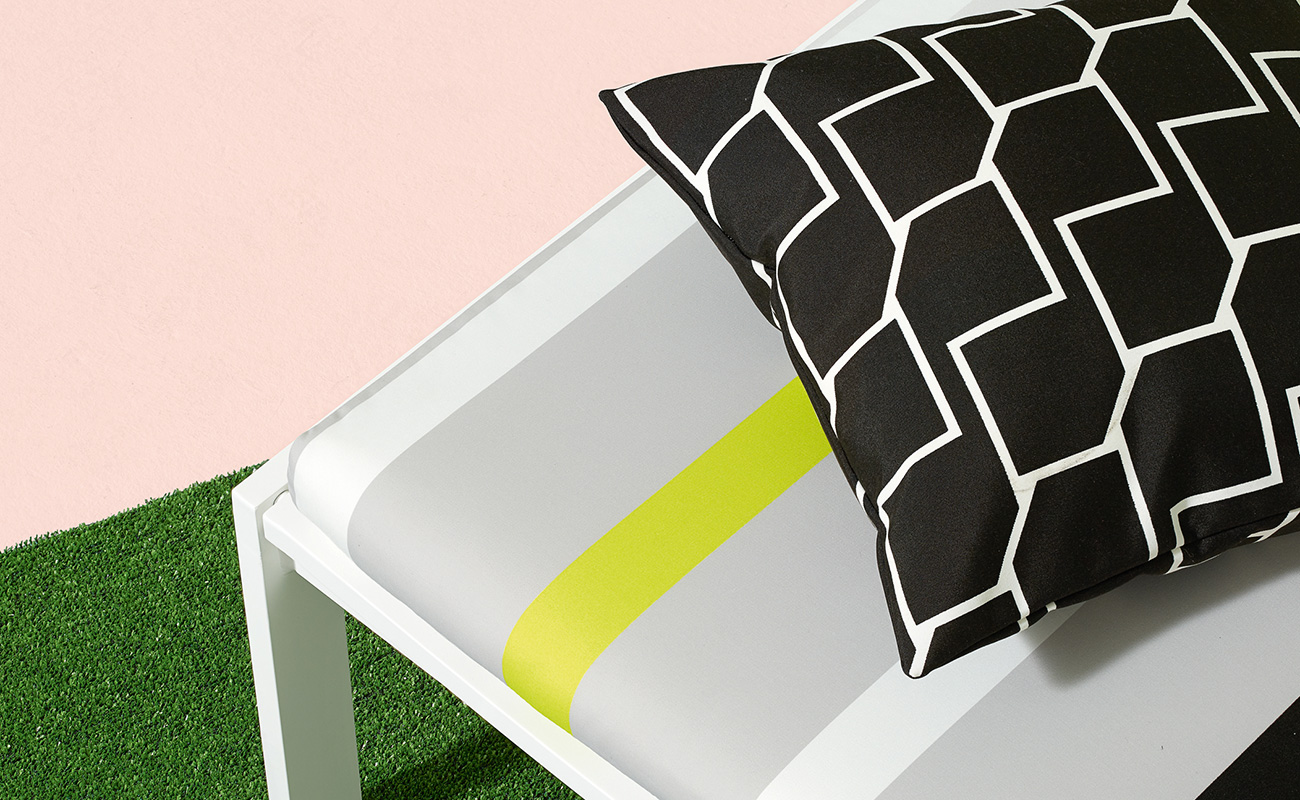 Black and white geometric patterned cushion against yellow, white and grey stripped outdoor seat