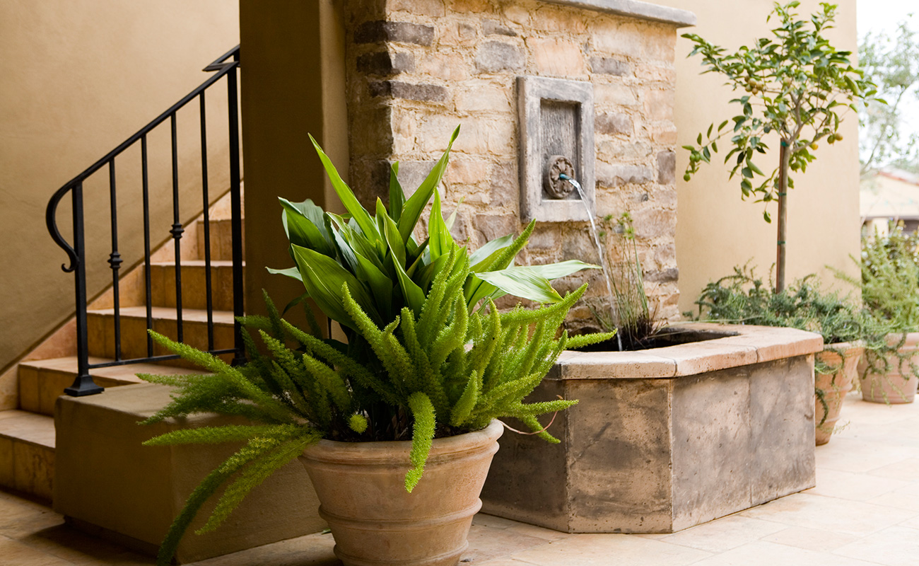 Spanish inspired garden with terracotta pots and fountain