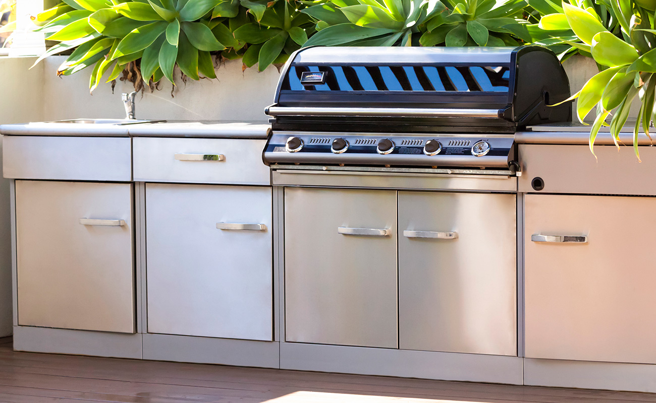Built-in stainless stell hooded barbeque unit with stroage and sink