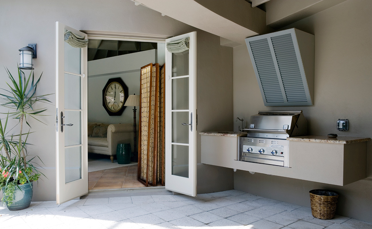 Basic outdoor kitchen with benchtop prepping space and hooded barbeque grill and ventilation