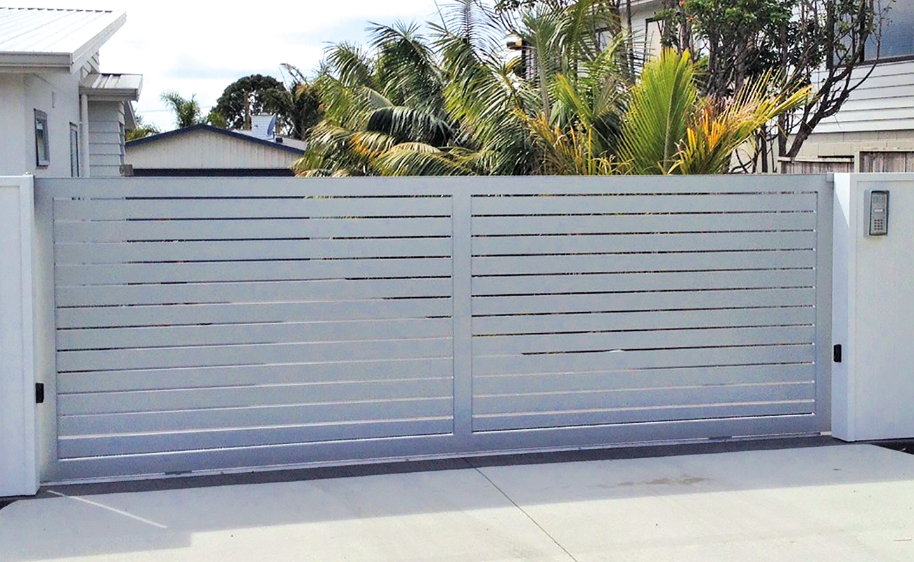 Modern slat style security gate with keypad and intercom.