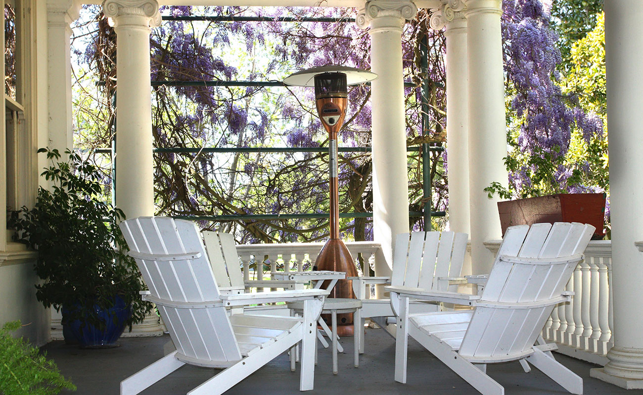 English style porch with white chairs and a heater