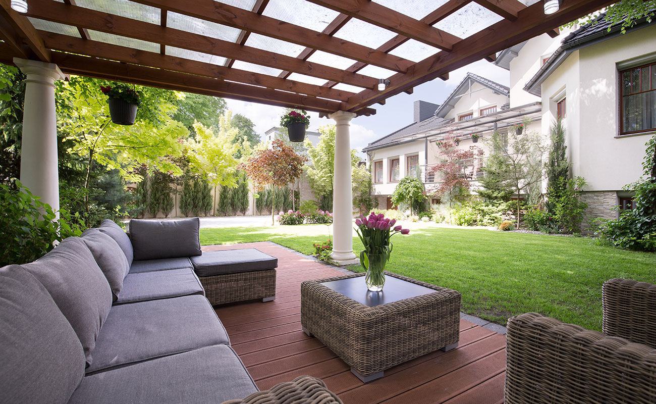 A classic outdoor room with couch set under a louvre roof