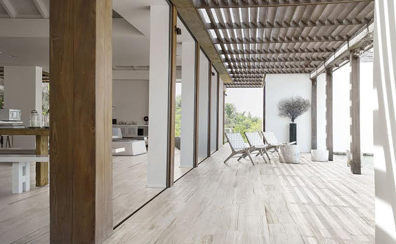 White outdoor area that is connected to the house with big windows that improve the indoor and outdoor flow