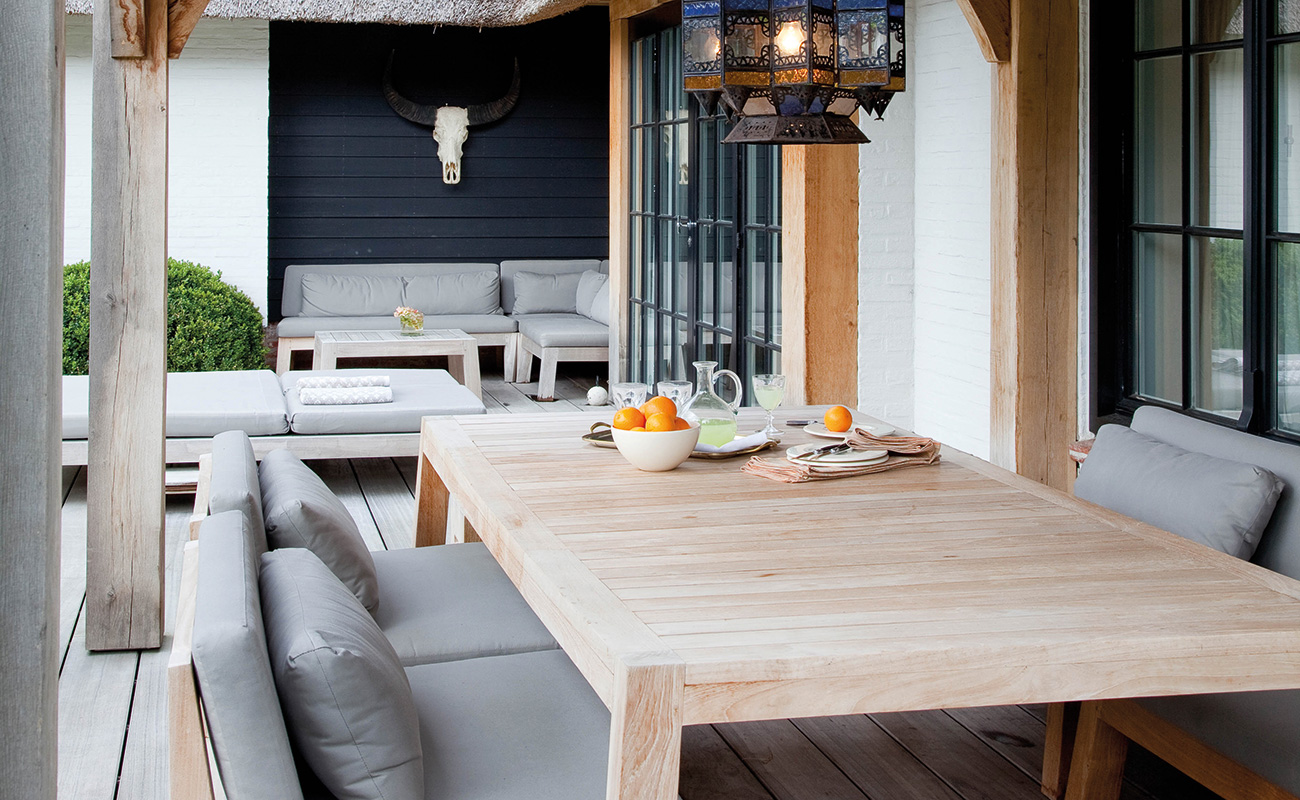 An outdoor dining area with cushioned chairs and wooden dining table with cups