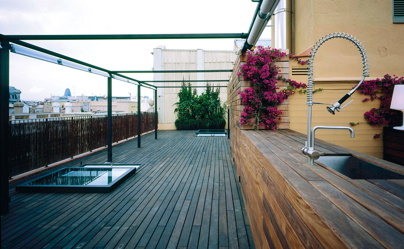 A wooden deck with an outdoor kitchen sink