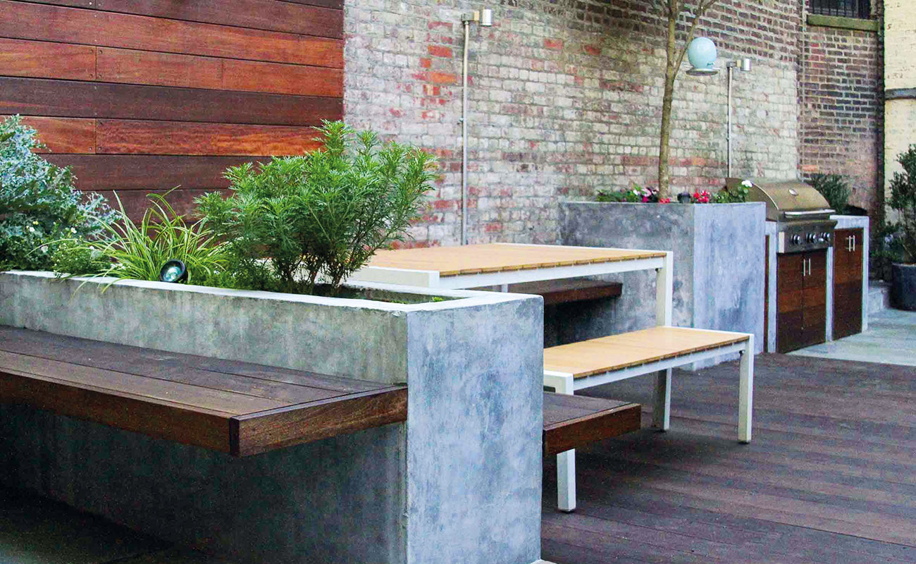 Outdoor kitchen with timber and benches and concrete plant boxes