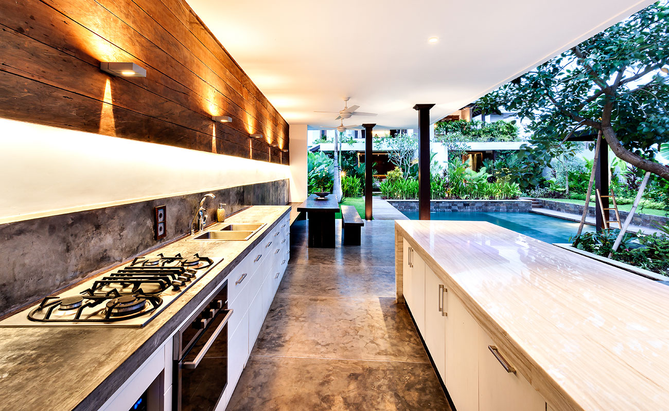 Modern outdoor kitchen next to a pool and garden