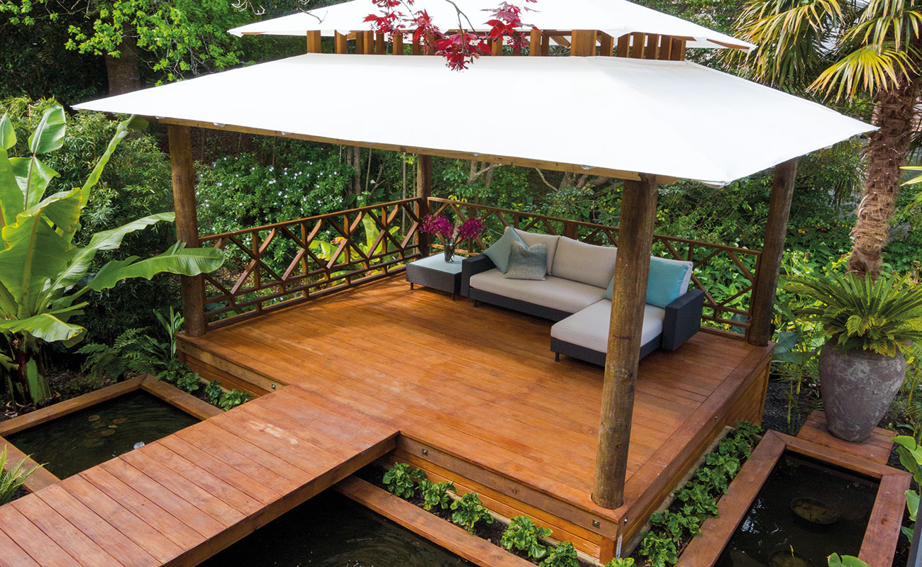 A covered deck area with a couch and surrounding plants