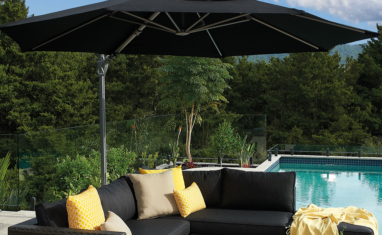 sun shade umbrella over a couch by a pool