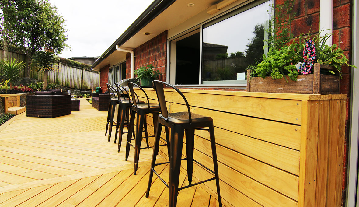 Bench with high chairs installed in large wooden deck