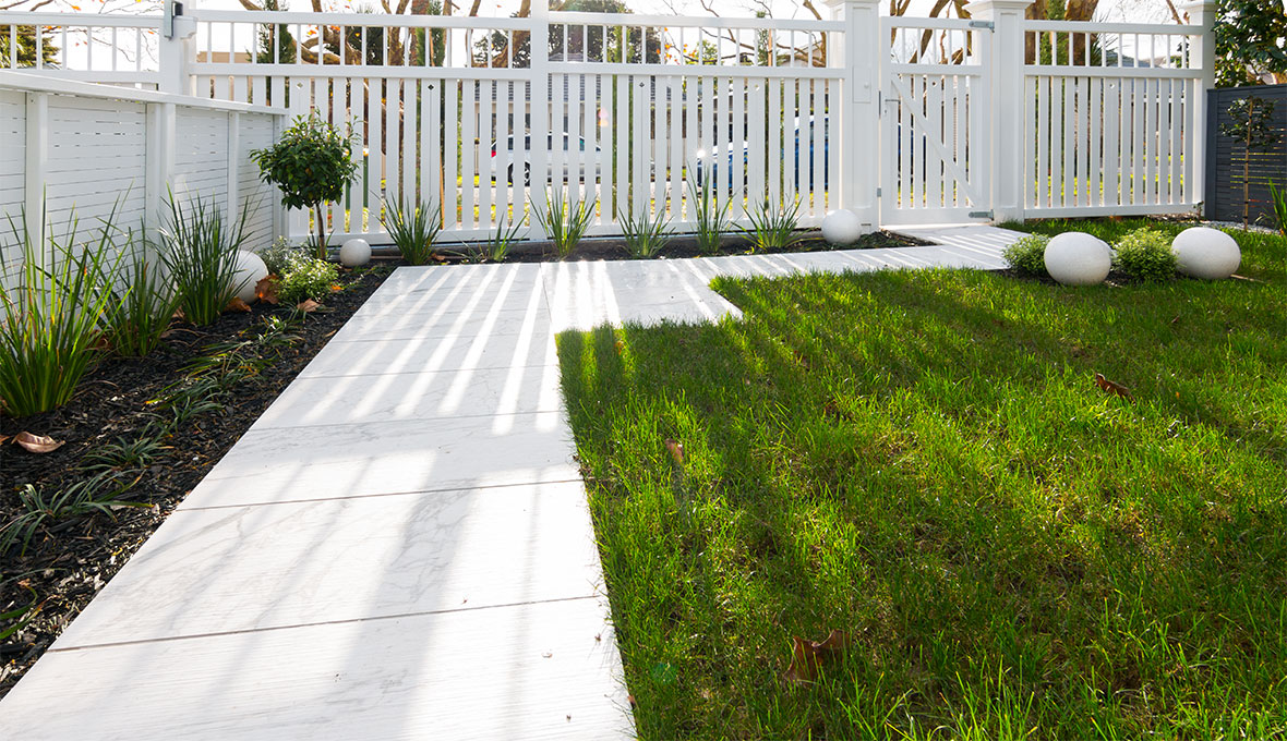 A concrete pathway and beautiful lawn