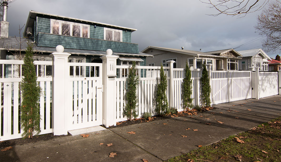 An overview of the house with new white fence and gate