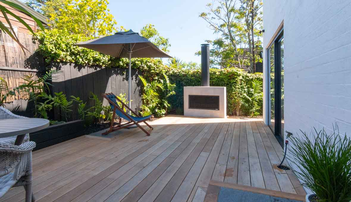 A complete backyard transformation in St Heliers with a deck, screens, hot tub, and fireplace!