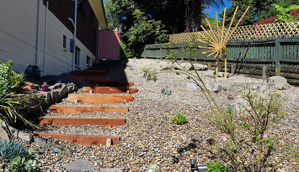 A steep low-maintenance garden with timber stairs