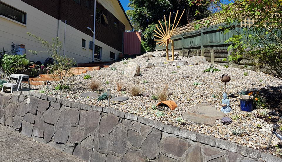 A steep low-maintenance garden with a rock wall