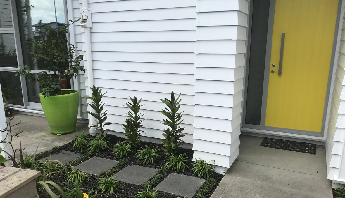 Landscaped entryway with yellow door