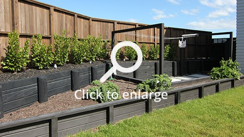 Raised vegetable garden bed surrounding clothes line section