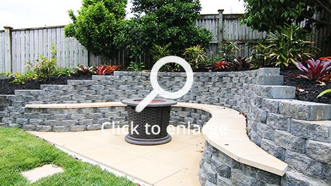 The fire pit is surrounded by a stylish bench supported on rock bricks