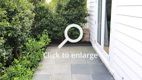 Concrete tiles surrounded by green bushes in front of a entry to the house