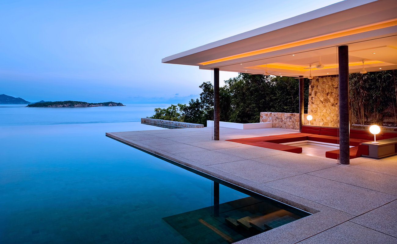 A beautiful outdoor couch area with a pool and outdoor lighting