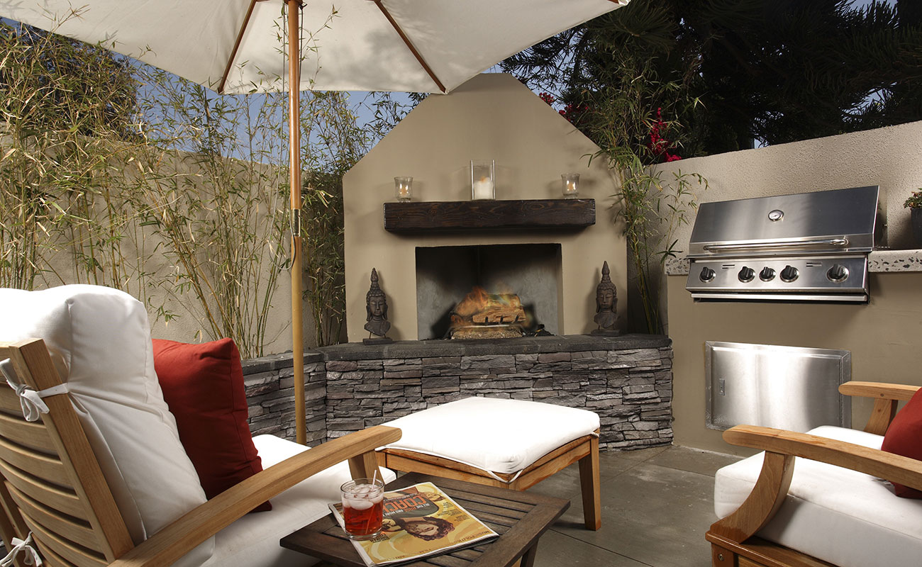 outdoor kitchen area with a fireplace, barbeque and an umbrella