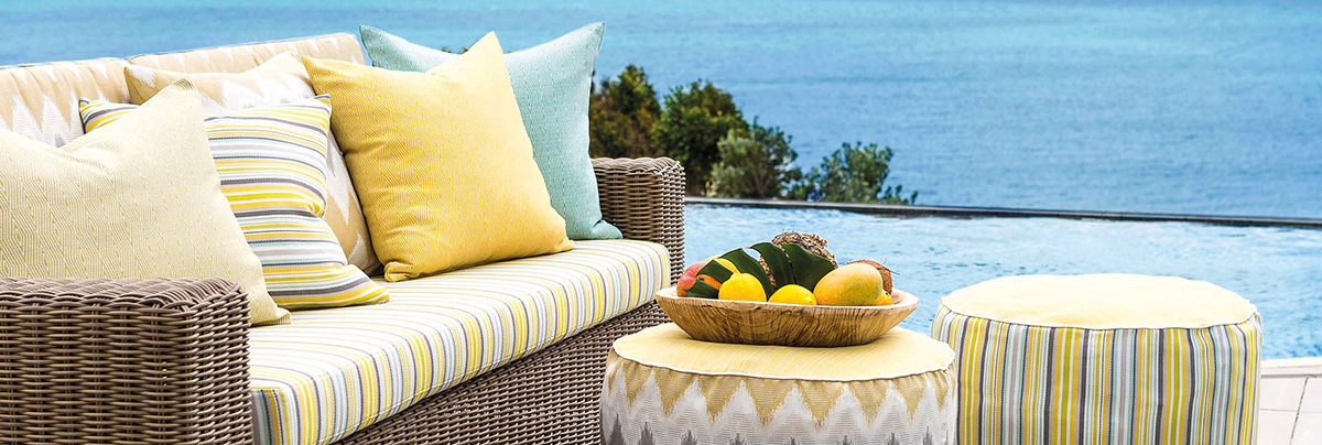 Outdoor wicker couch with yellow and grey patterned cushions and oversize floor cushions.