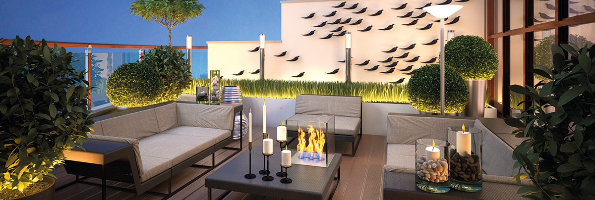 Inviting outdoor space at night with fire pit, up-lighting, candles, and outdoor furniture.