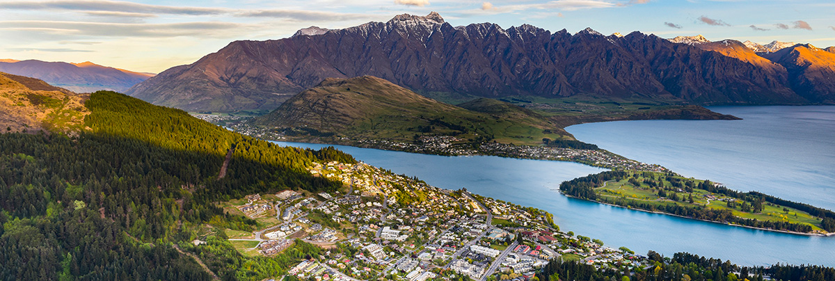 Aerial panoramic view of the center of Queenstown, Lake Wakatipu and surrounding mountains.