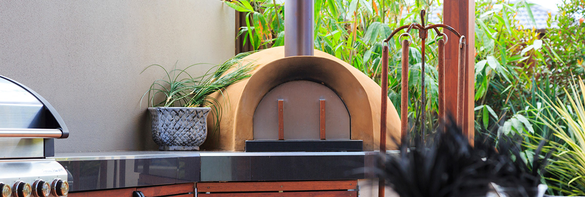 Basic outdoor kitchen with pizza oven and hooded barbeque