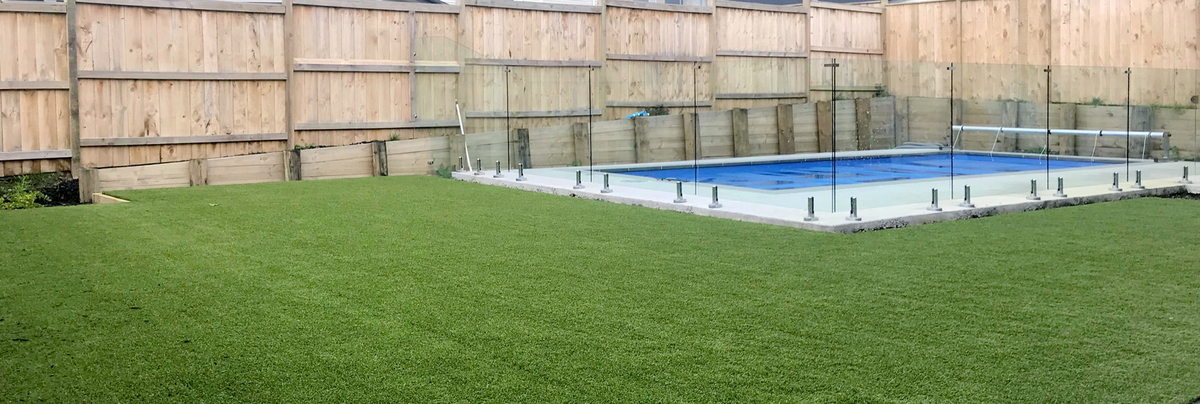 Artificial turf and swimming pool with glass boundary