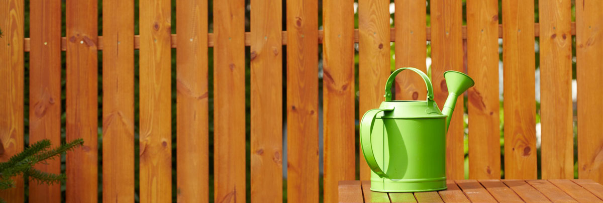 fence and green watering bucket