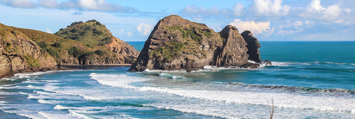 View of the ocean with waves and rocks in the background in Waitakere, West Auckland