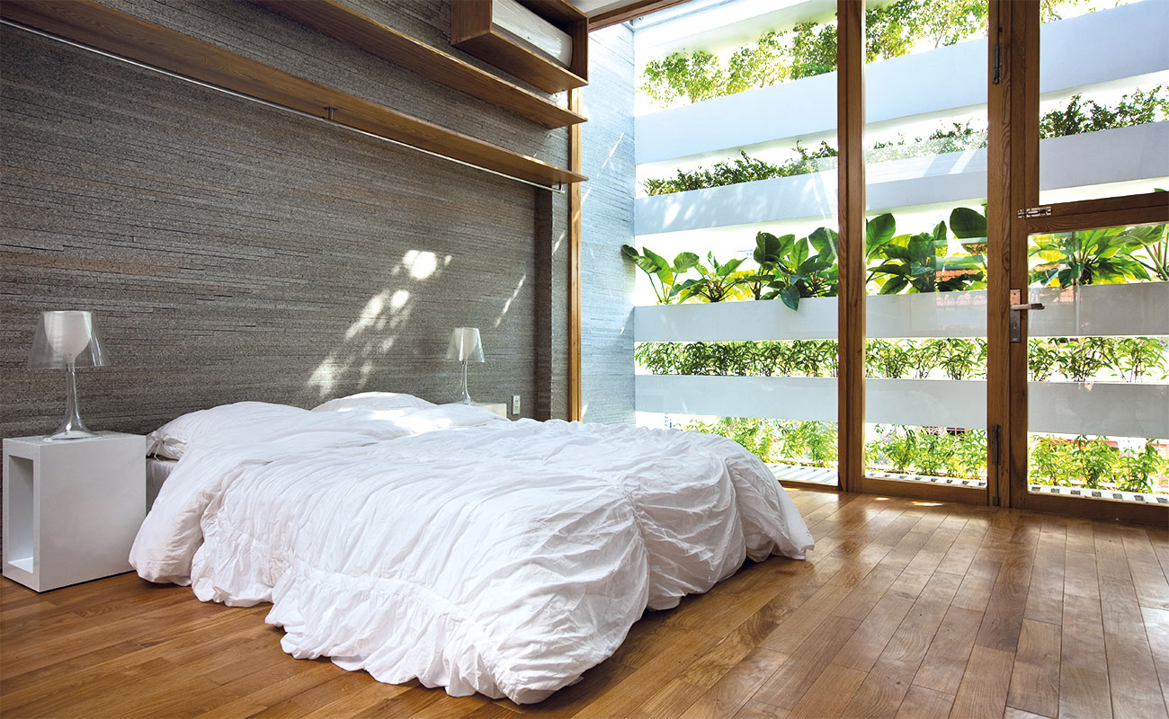 A bedroom with a balcony that is full of green plants