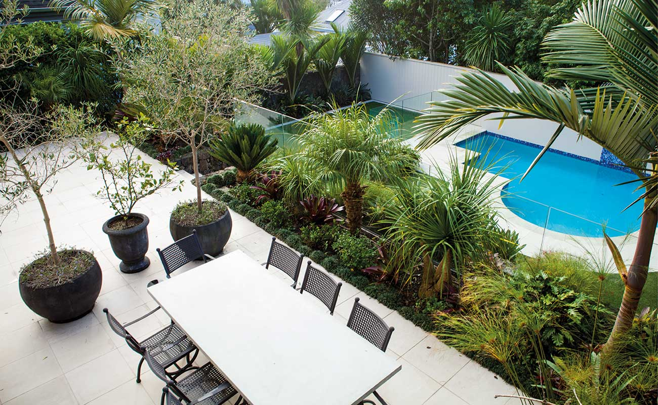 An garden with swimming pool, chairs and table where you can relax